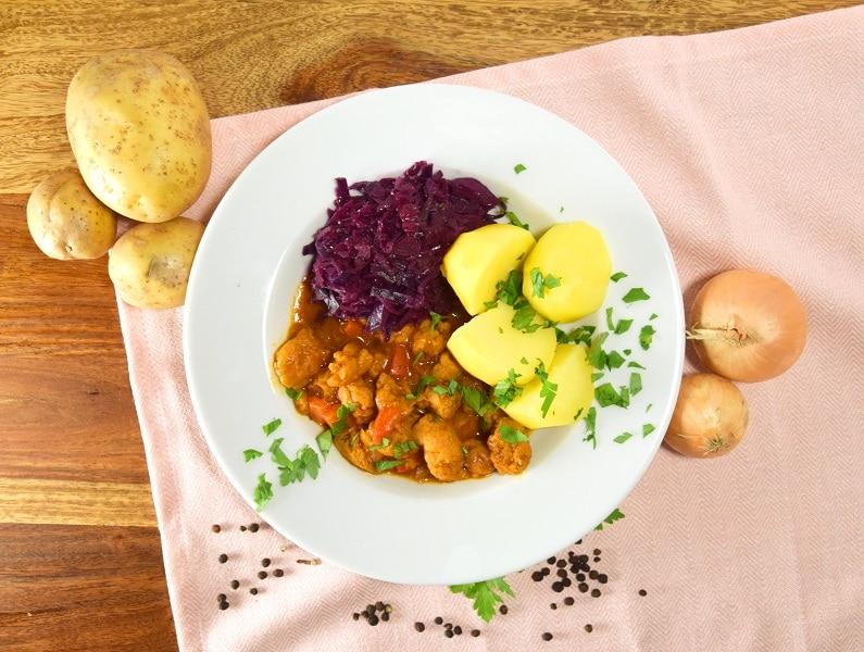 Teller mit Gulasch, Rotkohl und Salzkartoffeln