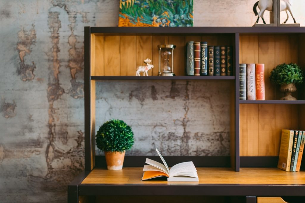 Un libro abierto sobre un escritorio con estantería.