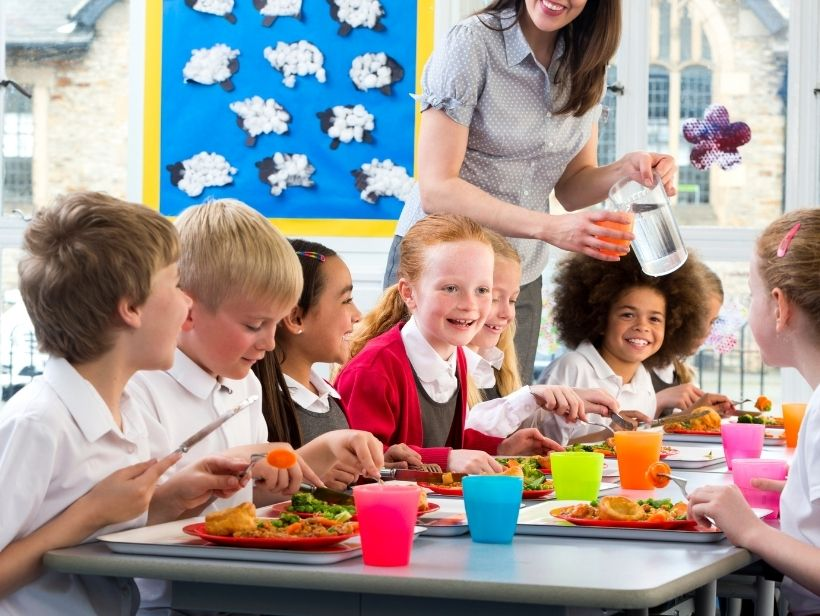 children eating around a table at school