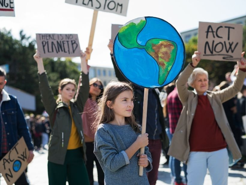 young girl holding a planet placard