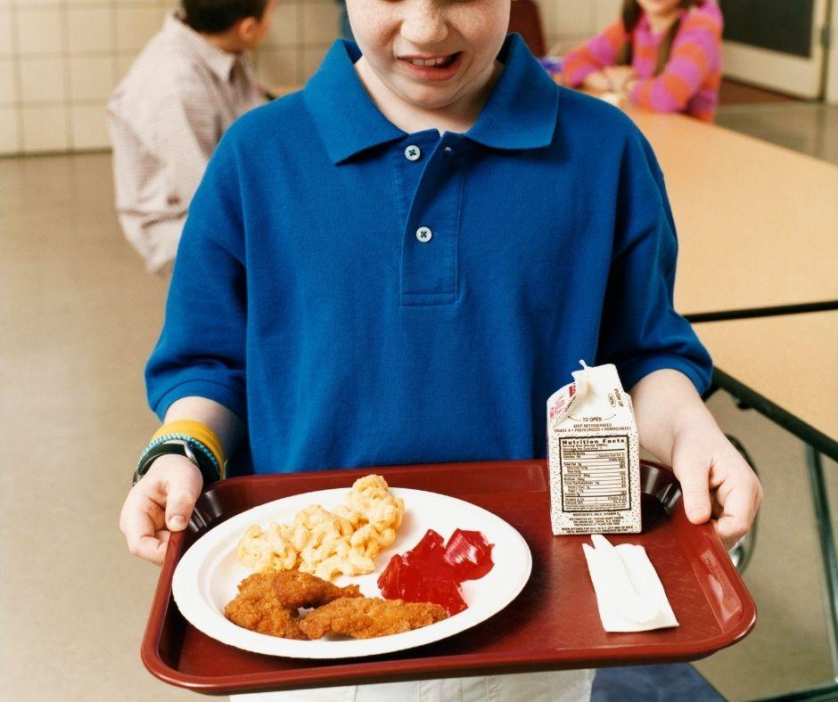 a boy holding a tray of unhealthy school food