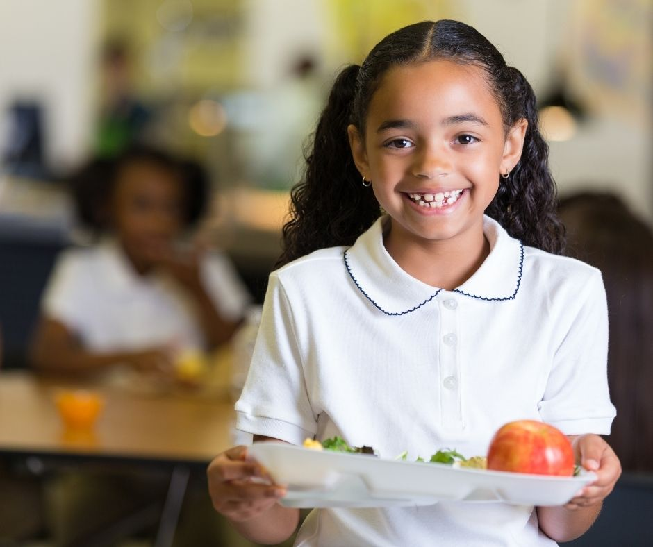 school child holding a plate of food
